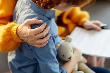 adult with protective arm around child holding a teddy bear